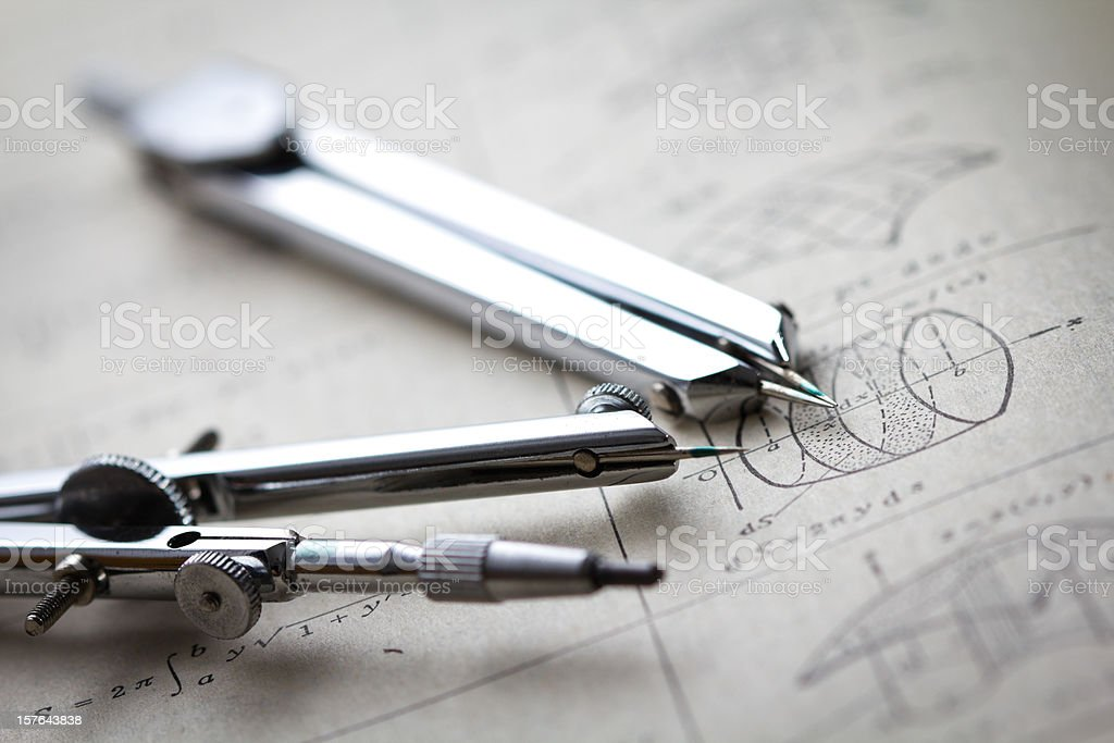 Two compasses on a math worksheet stock photo