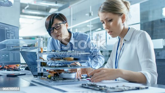 968289374istockphoto Two Computer Engineers Choose Printed Circuit Boards to Work with. In The Background Technologically Advanced Scientific Research Center. 968289554