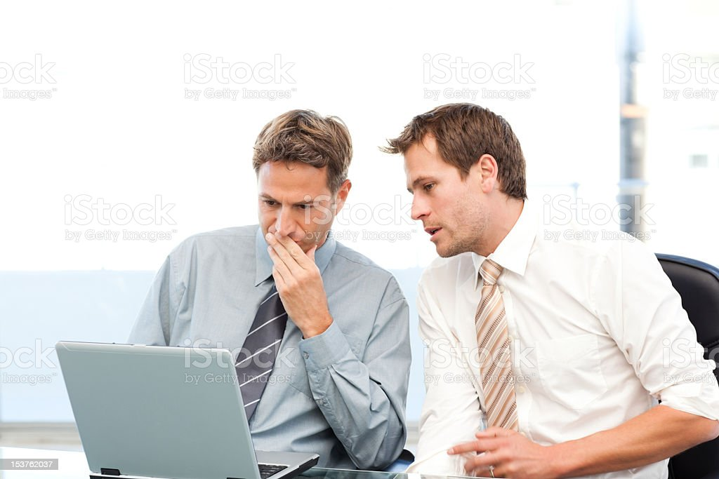Two concentrated businessmen working together on a laptop royalty-free stock photo