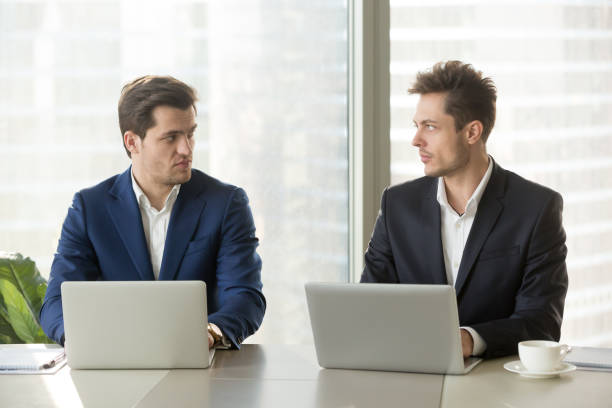 Two confident businessmen dislike each other, business competition and rivalry stock photo