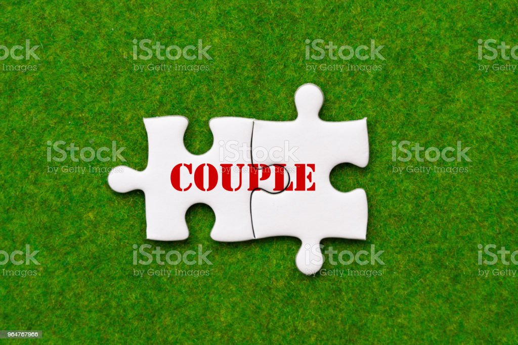 two connected jigsaw puzzle pieces with couple woring royalty-free stock photo