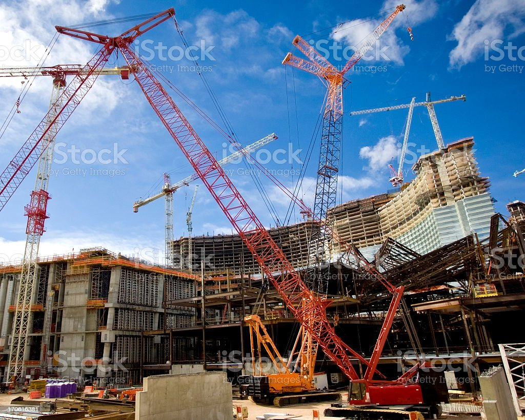 Two construction cranes on a large work site stock photo