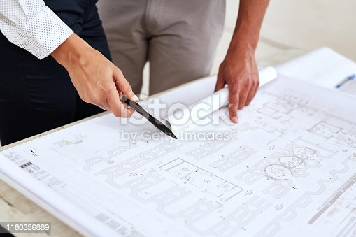 Closeup of two construction engineers standing over a table going over blueprints in detail together