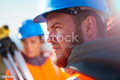 two surveyors using a builder's level to plan out the expansion of the wind farm site. they are wearing orange hi vis jackets and blue hard hats . one is male , one is female. they are in a rural landscape.