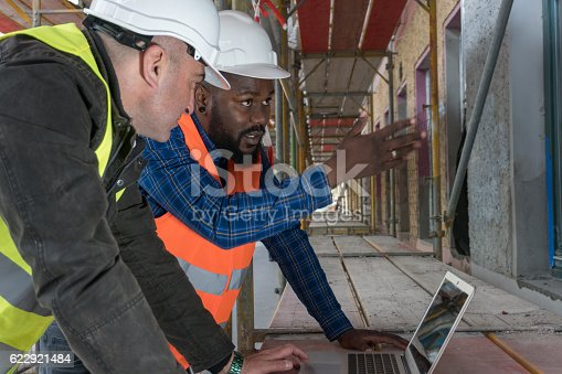 istock Two construction workers, an African american and a white 622921484