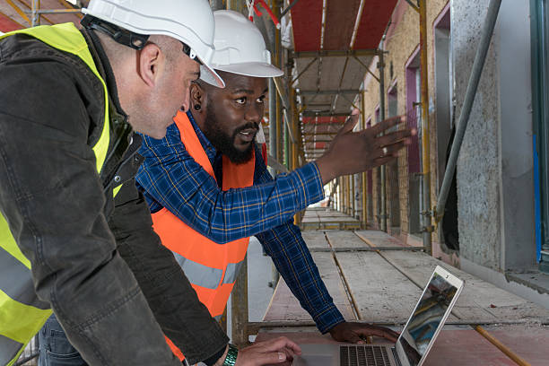 Two construction workers, an African american and a white Two construction workers, an African american and a white, wearing orange and yellow safety jackets and helmets among scaffolding on construction site foreman stock pictures, royalty-free photos & images