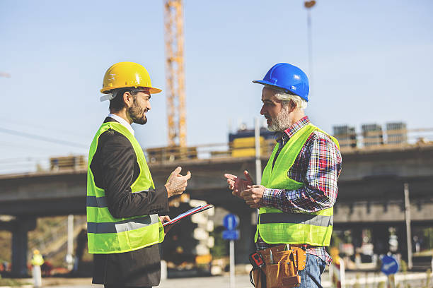 Two Construction Workers Discussing Two Construction Workers Discussing at construction site foreman stock pictures, royalty-free photos & images