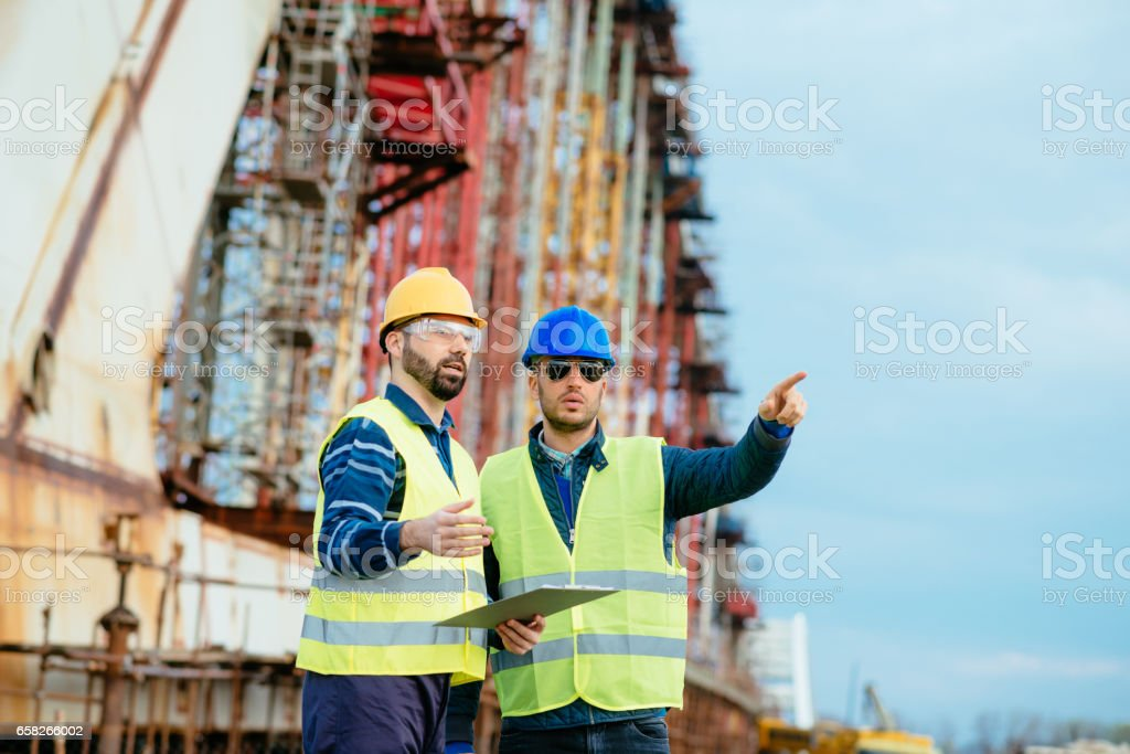 Engineering on construction site. Engineers building bridge over...