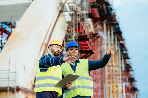 two construction workers - engineers on construction site agreeing upon next building phase - civil engineer stock photos and pictures