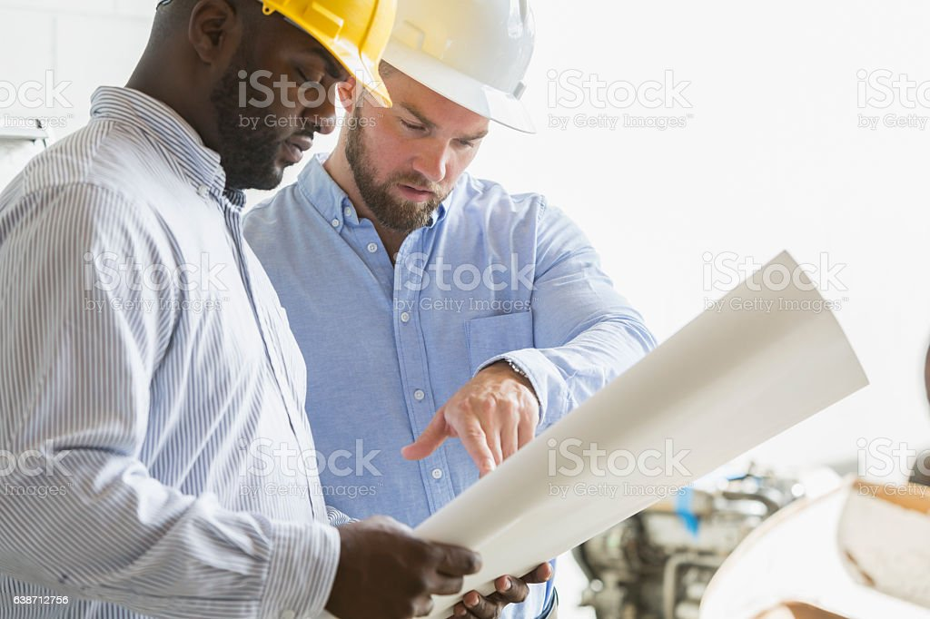 Two construction workers looking at plans stock photo