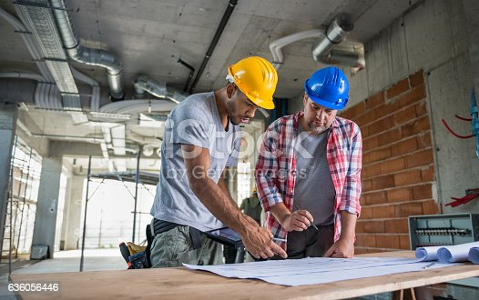 istock Two Construction Workers Looking Blueprint Together 636056446