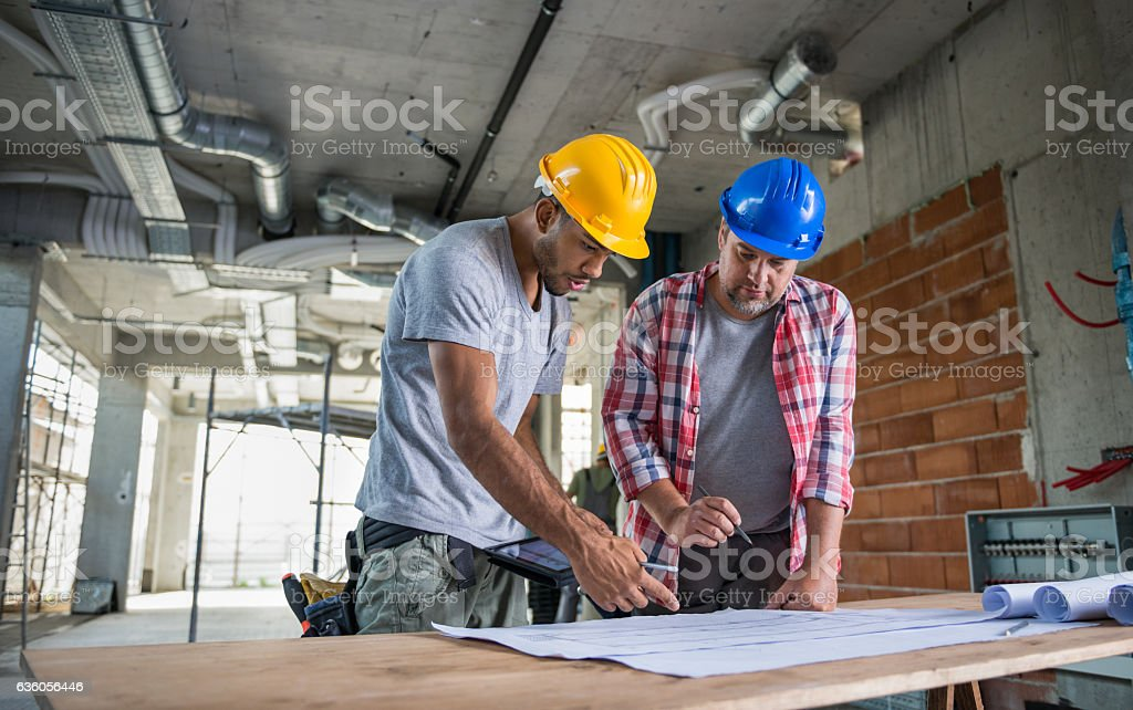 Two Construction Workers Looking Blueprint Together stock photo
