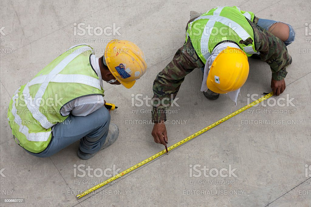Two construction workers measure out guide lines for laying a raised...