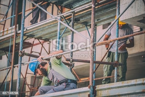 Front view of two workers on scaffolding.