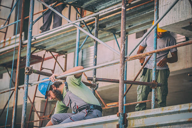 Two construction workers on scaffolding Front view of two workers on scaffolding. scaffolding stock pictures, royalty-free photos & images