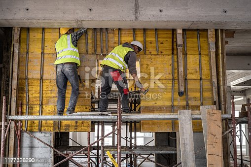 Rear view of two construction workers in reflective vests and hardhats working on raised scaffolding.