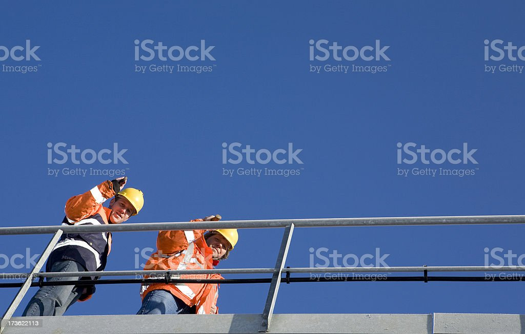 Two constructionworkers on a bridge stock photo