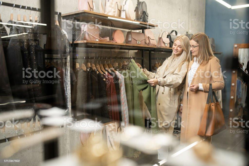 Zwei moderne stilvolle Frauen stehen am Rack, während sie neue Hosen wählen - Lizenzfrei Arbeiten Stock-Foto