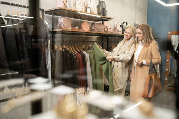 Dos mujeres con estilo contemporáneo de pie por estante mientras eligen pantalones nuevos - foto de stock