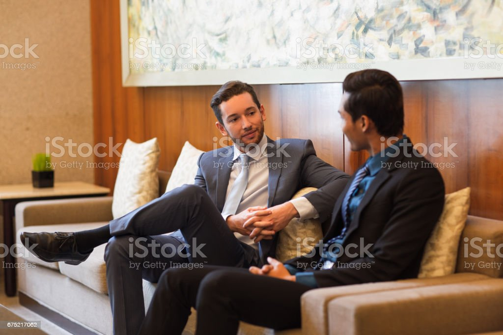 Two Content Business Men Chatting in Lounge stock photo