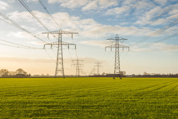 Two converging high-voltage lines in a rural area Backlit image of two converging high voltage lines in a rural Dutch landscape in the fall season. electricity pylon stock pictures, royalty-free photos & images
