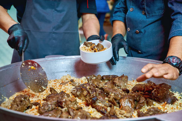 Two cooks in uniform prepare Uzbek pilaf from lamb. Plav is an excellent dish and cooked on the grill in the open air. Two cooks in uniform prepare Uzbek pilaf from lamb. Plav is an excellent dish and cooked on the grill in the open air. close-up muziekfestival stock pictures, royalty-free photos & images
