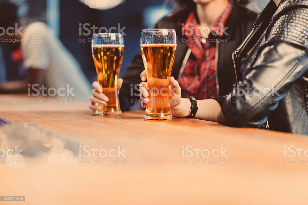 Two cool girls drinking beer in a pub – Foto