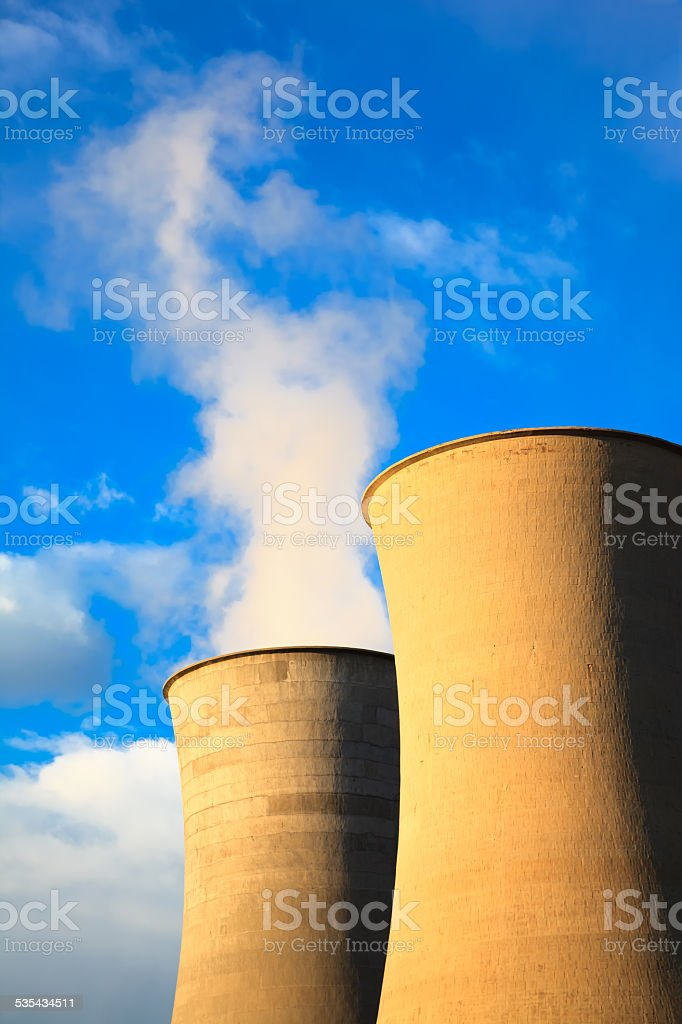Two cooling tower in geothermal energy power station on sunset. stock photo