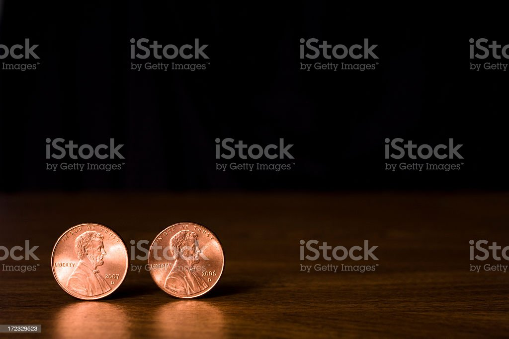 Two copper Lincoln head pennies against black background stock photo