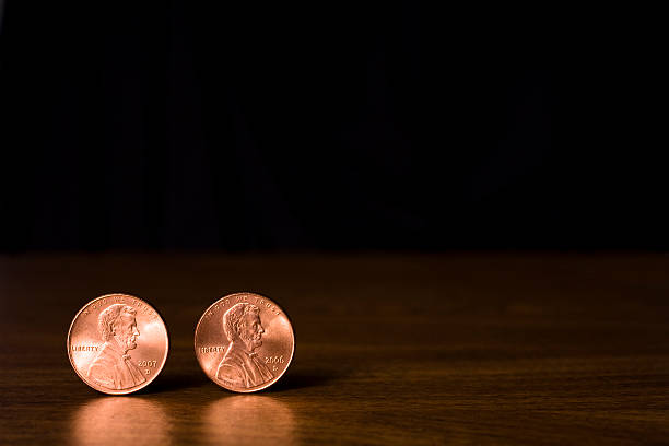two copper lincoln head pennies against black background - 美國硬幣 個照片及圖片檔