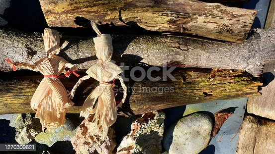 Two handmade corn husk dolls on a background with wood logs and stones, autumn harvesting decoration, pagan symbols.