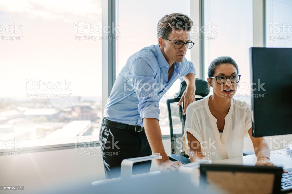 Two corporate professionals working together on computer stock photo