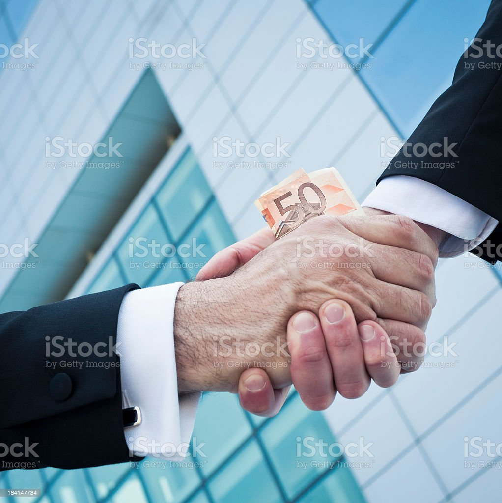 Two Corrupted Men Shaking Hands  Against  A Modern Skyscraper stock photo