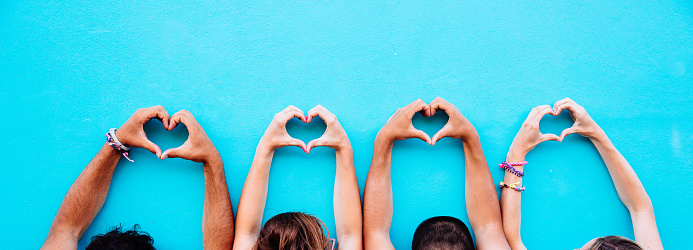 Two couple making heart shape from hand on blue background