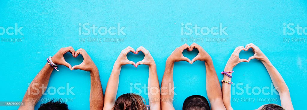 Two couple making heart shape from hand stock photo