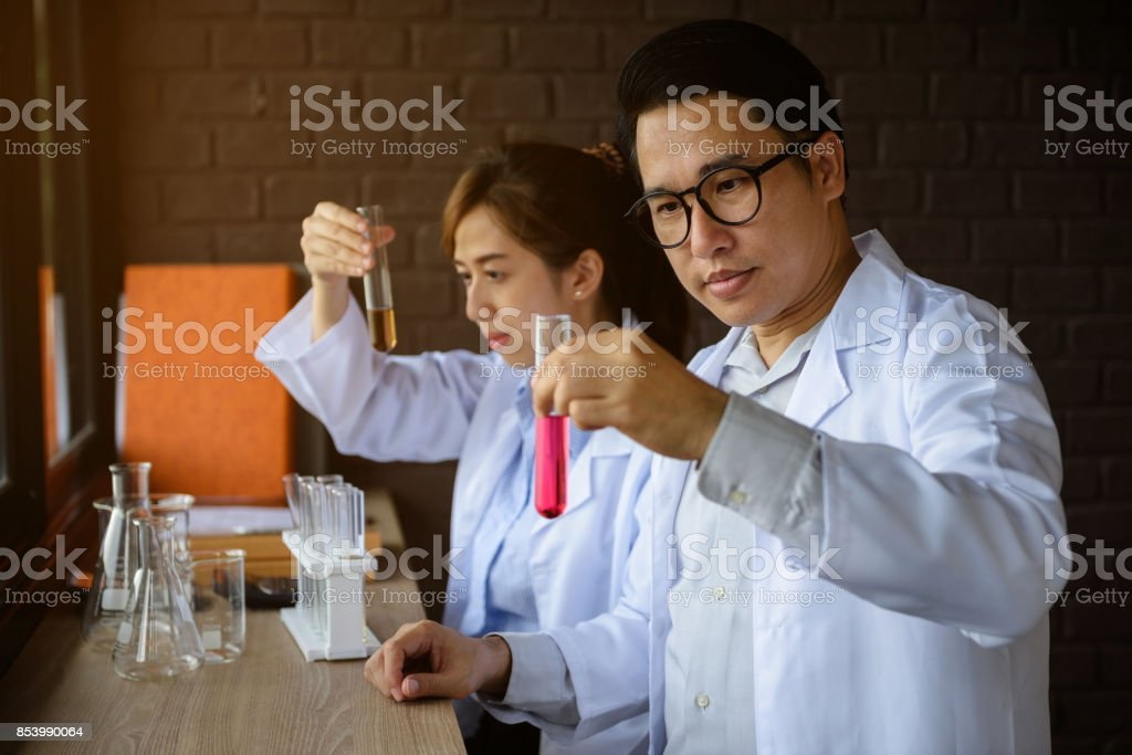 Two couple scientist man and woman test liquid substance in test tube...
