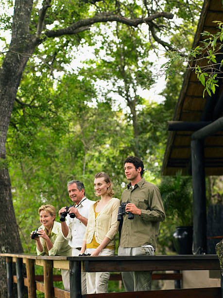 Two couples at lodge, three holding binoculars, smiling stock photo