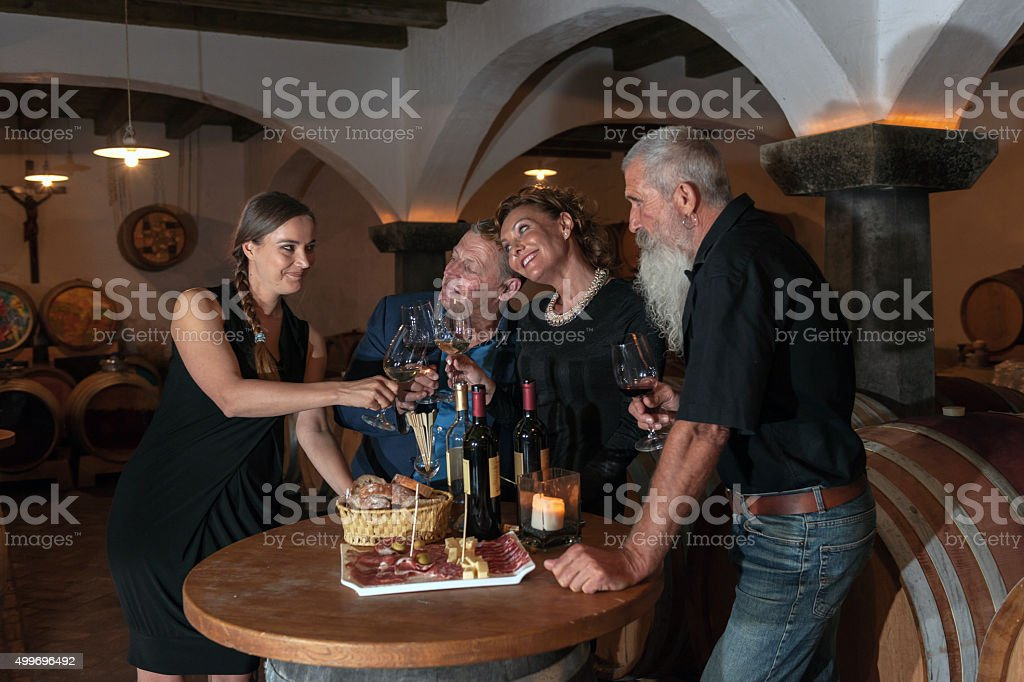 Two Couples Enjoying Food and Red Wine, Cellar in Europe stock photo