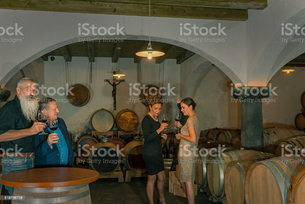 Two Couples Enjoying Red Wine, Cellar in Europe stock photo