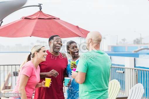 istock Two couples hanging out on pool deck, talking, laughing 1023462474