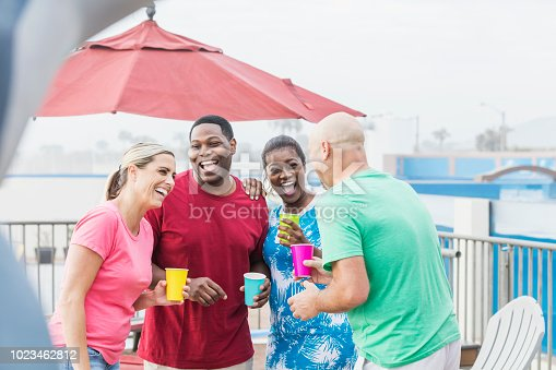 istock Two couples hanging out on pool deck, talking, laughing 1023462812