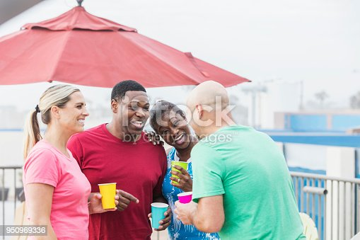 istock Two couples hanging out on pool deck, talking, laughing 950969336