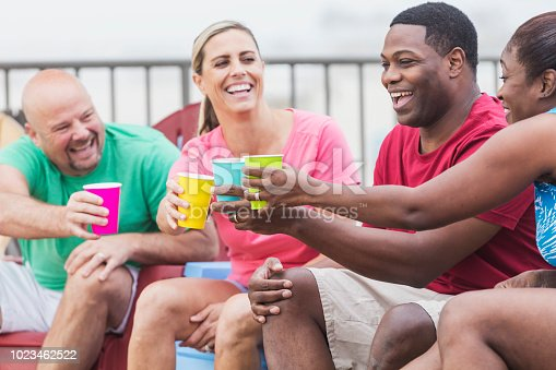 istock Two couples hanging out on pool deck, talking, toasting 1023462522