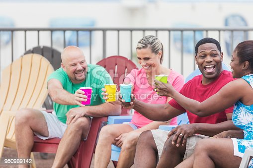 istock Two couples hanging out on pool deck, talking, toasting 950969142