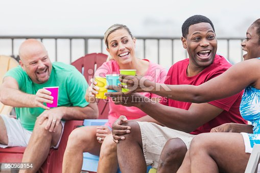 istock Two couples hanging out on pool deck, talking, toasting 950969154