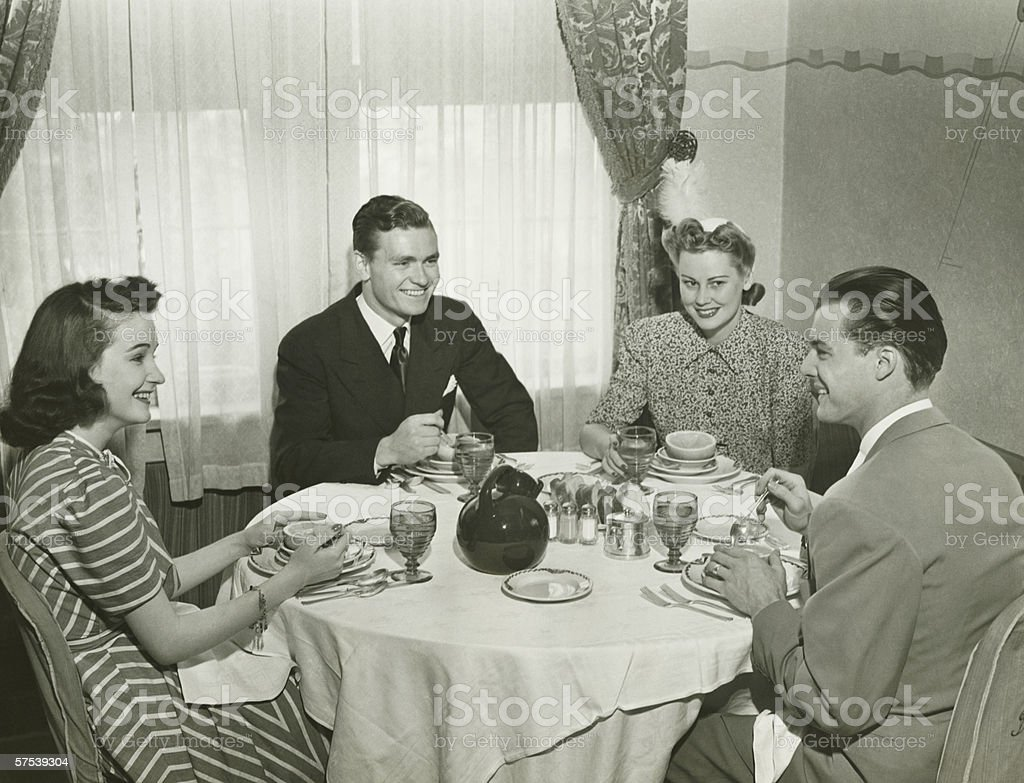 Two couples having dinner, (B&W) stock photo