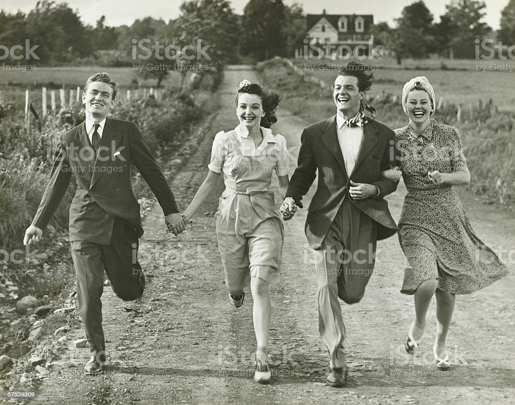 Two couples holding hands, running on footpath, (B&W) royalty-free stock photo