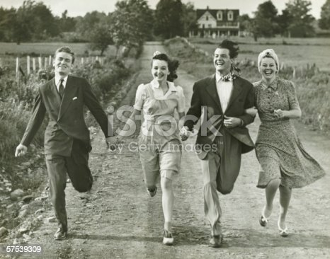 istock Two couples holding hands, running on footpath, (B&W) 57539309