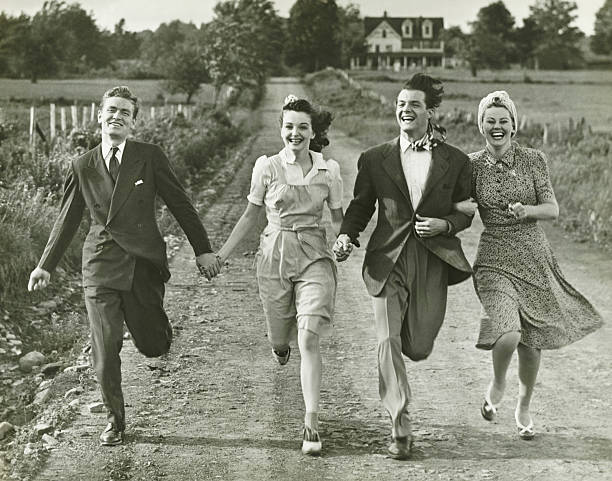 Two couples holding hands, running on footpath, (B&W) stock photo