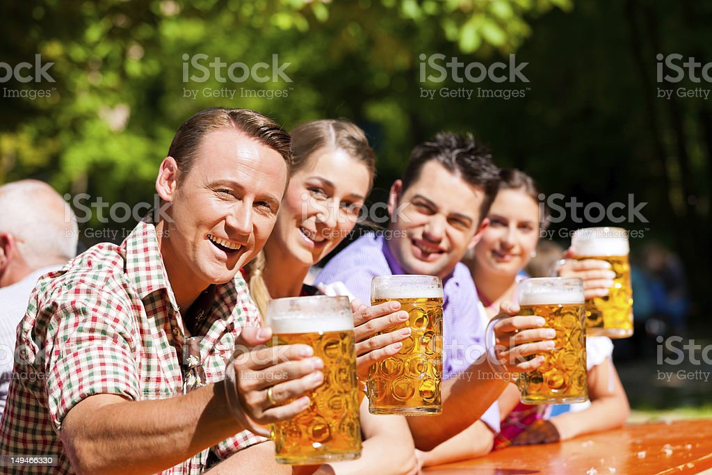 Two couples holding mugs of beer in a beer garden stock photo